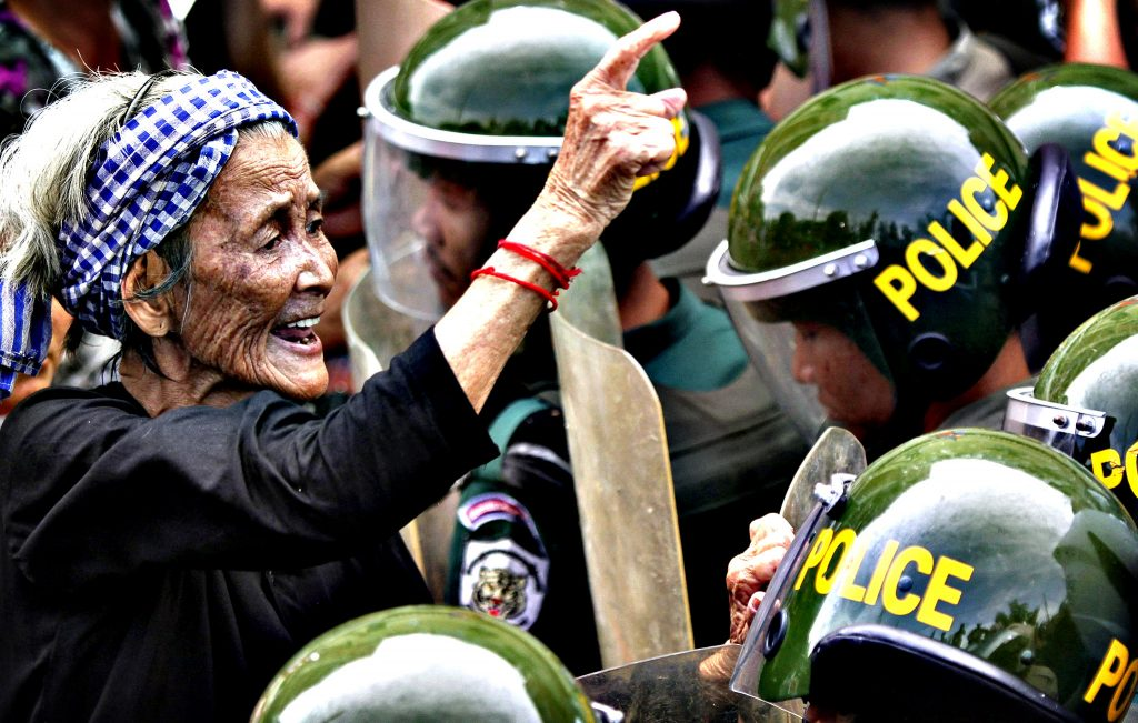 A woman gestures at police officers blocking a street during a protest in Phnom Penh...A woman gestures at police officers blocking a street during a protest in Phnom Penh June 17, 2013. The residents of Boeung Kak Lake have been embroiled in a long-running land dispute with a real estate development firm in the capital, and are also appealing for the release of another resident, Yorm Bopha, from prison. REUTERS/Samrang Pring (CAMBODIA - Tags: CRIME LAW CIVIL UNREST POLITICS)
